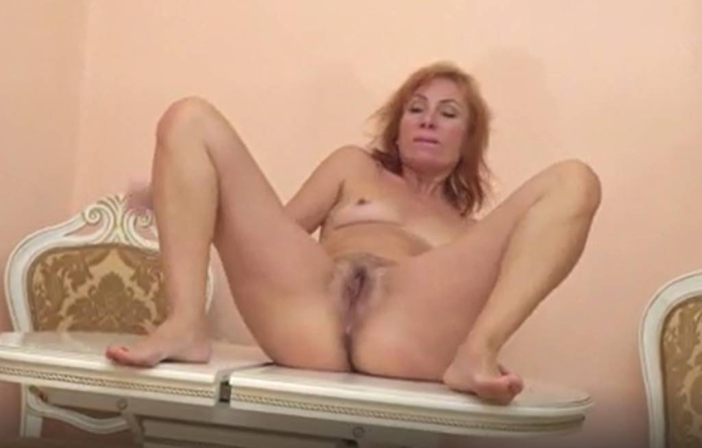 Granny redhead showing her hairy beaver and small tanlined boobs